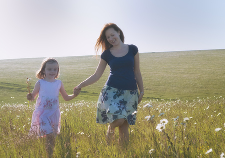 selections: Mother and daughter walking in field LANG_EVOIMAGES