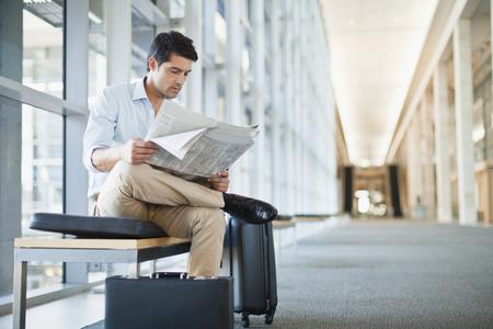 Businessman reading newspaper on bench LANG_EVOIMAGES