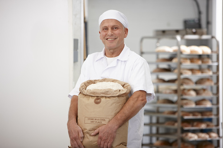 Chef carrying sack of flour in kitchen LANG_EVOIMAGES