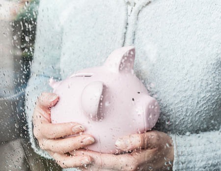 saturating: Woman with piggy bank at rainy window