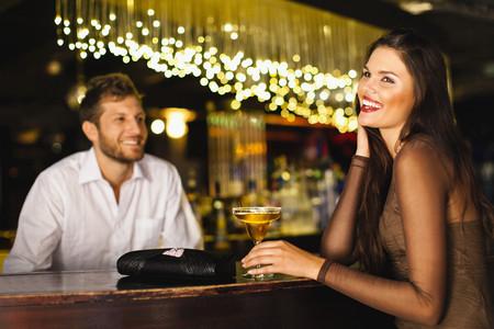 Woman talking to bartender at bar