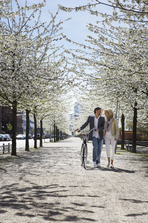flowered: Couple walking bicycle in park