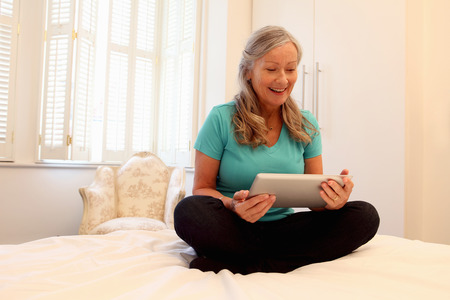 grays: Older woman using tablet computer on bed LANG_EVOIMAGES