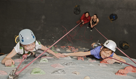 a rehearsal: Girls climbing indoor rock wall LANG_EVOIMAGES