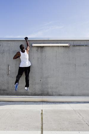 dangling: Man scaling wall on city street