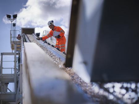 mined: Worker examining stones on conveyor belt