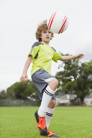 Boy playing with soccer ball in field