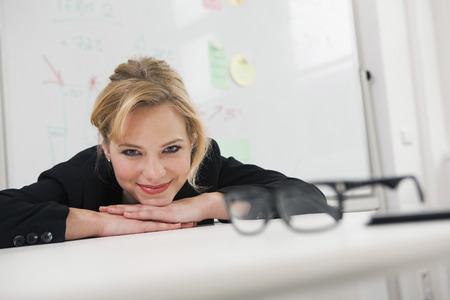 Businesswoman resting chin on desk