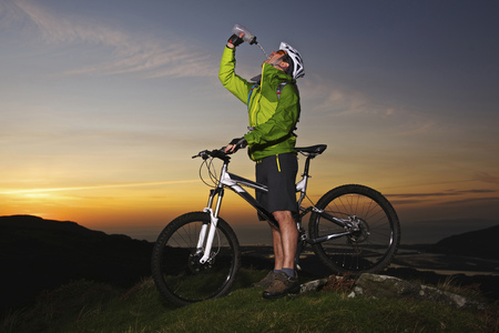Mountain biker drinking water on hilltop