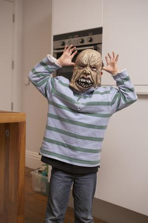 dressups: Boy wearing Halloween mask in kitchen LANG_EVOIMAGES