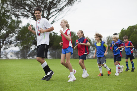 a rehearsal: Coach training children on field