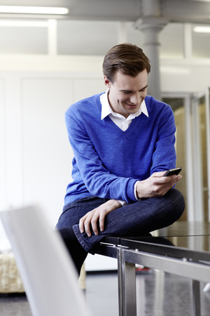 Businessman using cell phone on desk