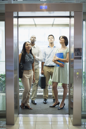 dubious: Business people riding glass elevator LANG_EVOIMAGES