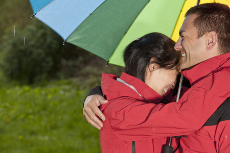 hardships: Couple hugging under rainbow umbrella