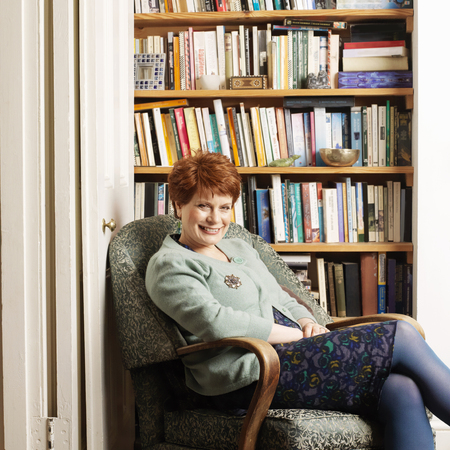 tomes: Smiling woman sitting in armchair LANG_EVOIMAGES