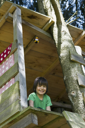 low spirited: Smiling boy sitting in tree house