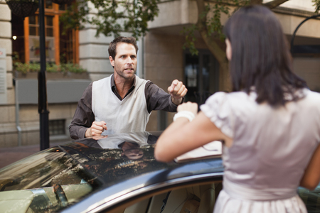 confrontational: Couple arguing over sports car LANG_EVOIMAGES