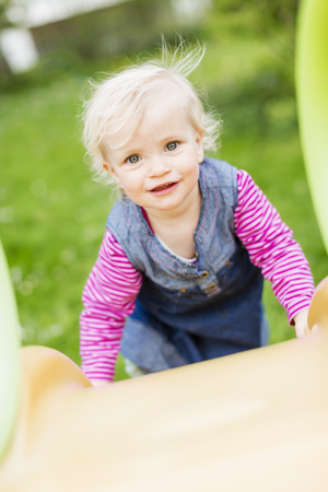 ascends: Toddler girl climbing slide in backyard LANG_EVOIMAGES