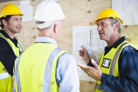 Arbeiter lesen Blaupausen vor Ort LANG_EVOIMAGES