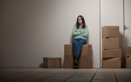 hardships: Teenage girl sitting on cardboard box