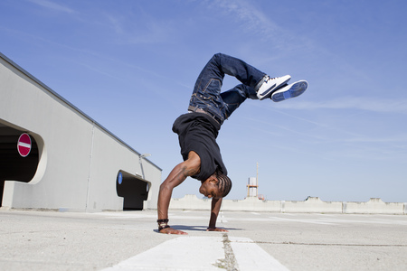 Man doing handstand on rooftop LANG_EVOIMAGES
