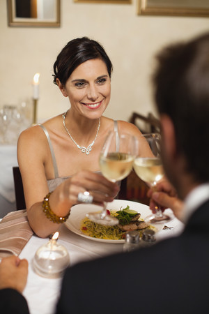 welldressed: Couple toasting each other in restaurant LANG_EVOIMAGES