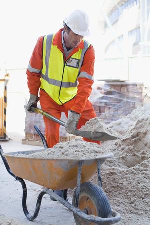 Worker shoveling concrete on site LANG_EVOIMAGES