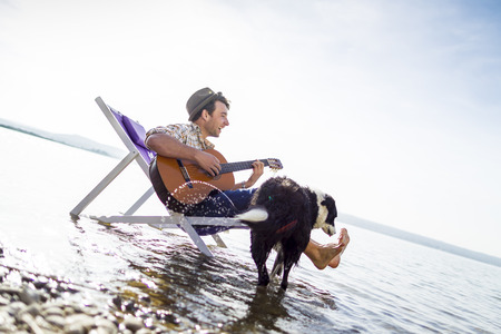musically: Man with dog in lawn chair in creek