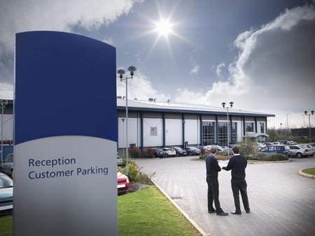 carbon neutral: Businessmen standing in parking lot