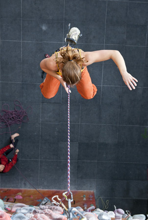 rockclimber: Climber falling into the rope at climbers gym