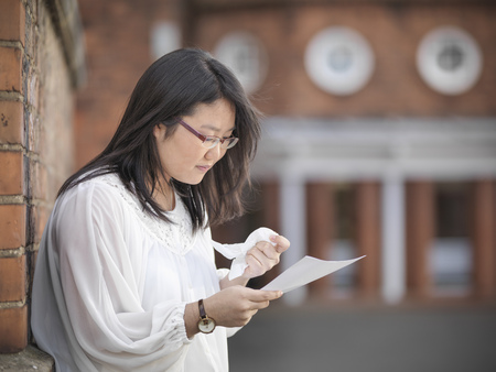 Crying student reading grades at school LANG_EVOIMAGES