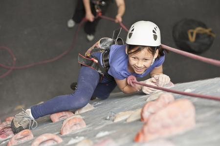 scaling: Girl climbing indoor rock wall
