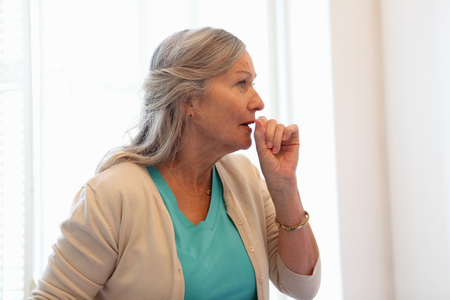 grays: Older woman coughing into her hand LANG_EVOIMAGES