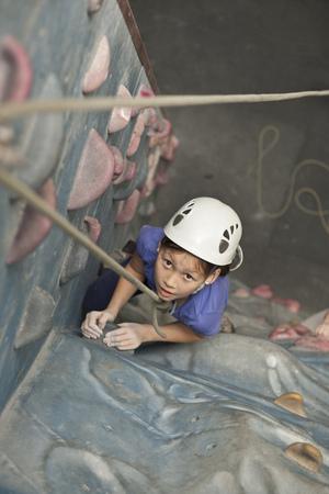 rockclimber: Girl climbing indoor rock wall