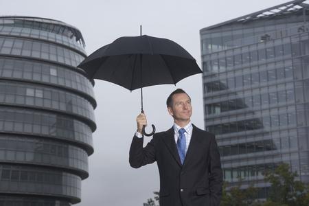 rains: Businessman standing under umbrella