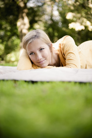 lays down: Woman laying on blanket in park