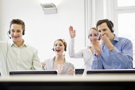 handsfree telephones: Business people cheering in headsets