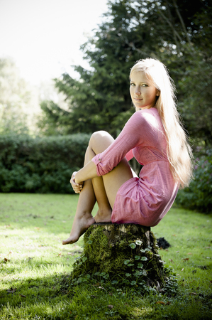 frock: Woman sitting on stump outdoors LANG_EVOIMAGES