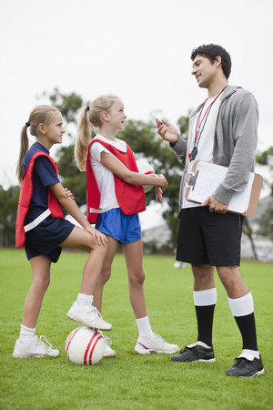 Coach talking to children on soccer team