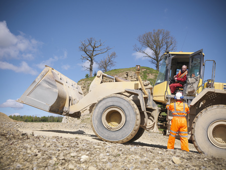 Workers talking on digger in quarry LANG_EVOIMAGES