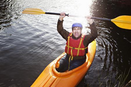 Kayaker holding oar in still lake LANG_EVOIMAGES