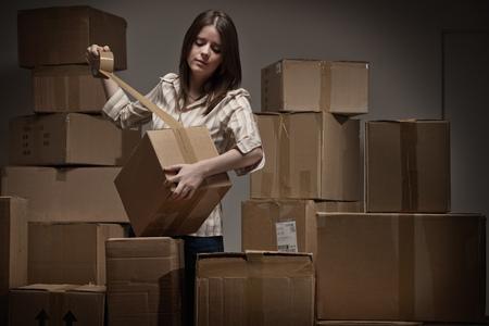 sellotape: Teenage girl taping up cardboard boxes