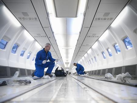 Worker examining empty airplane