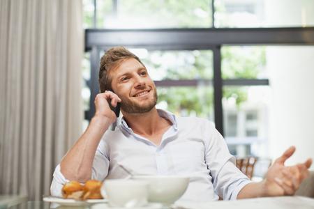reconocimientos: Hombre hablando por teléfono celular en el desayuno LANG_EVOIMAGES
