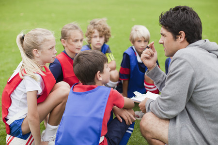 instructs: Coach talking to childrens soccer team