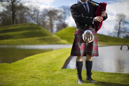 Man in Scottish kilt playing bagpipes