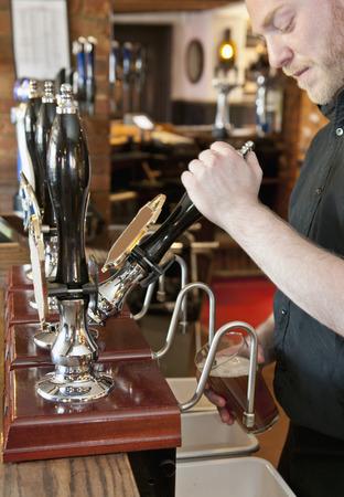 Bartender pouring beer at bar