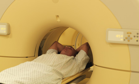 arms behind head: Man relaxing in MRI machine