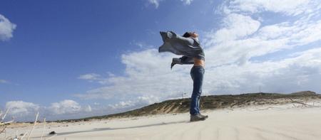 Woman standing on windy beach