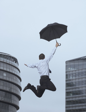 drizzling rain: Businessman jumping for joy outdoors LANG_EVOIMAGES